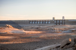 The dam is seen beyond stretches of bare lake bottom.