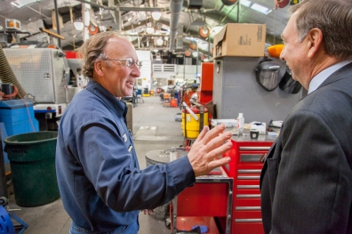 The City Manager is greeted by an employee at vehicle maintenance and repair bay.