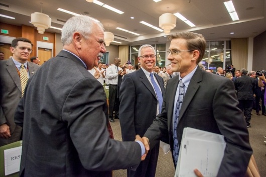 Project Manager Desmond Parrington and City Treasurer Russ Fehr shake hands as John Dangerberg smiles in background just after City Council approved staff recommendations to move forward on the Entertainment & Sports Center Project.