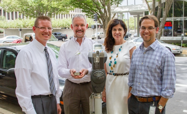 "Matt Eierman, Mike King, Linda tucker, and Carlos Eliason photographed with award next to a ""smart"" meter in downtown."