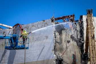 A worker sprays water on the structure being demolished, to reduce dust particles in the air.