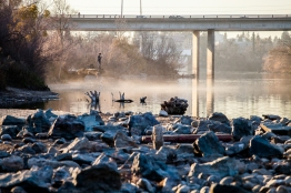 A citizen observes low water levels on the American River near Watt Ave.