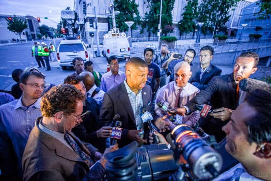 Mayor Kevin Johnson stands amidst a media scrum on the first day of the downtown plaza mall is being partially demolished.