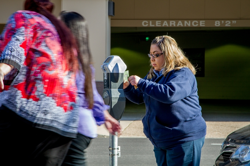 Parking Services staff Hortencia Martinez installs Parkmobile stickers on meters around Cesar Chavez Plaza.