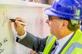 City Manager John Shirey signs his name on the beam